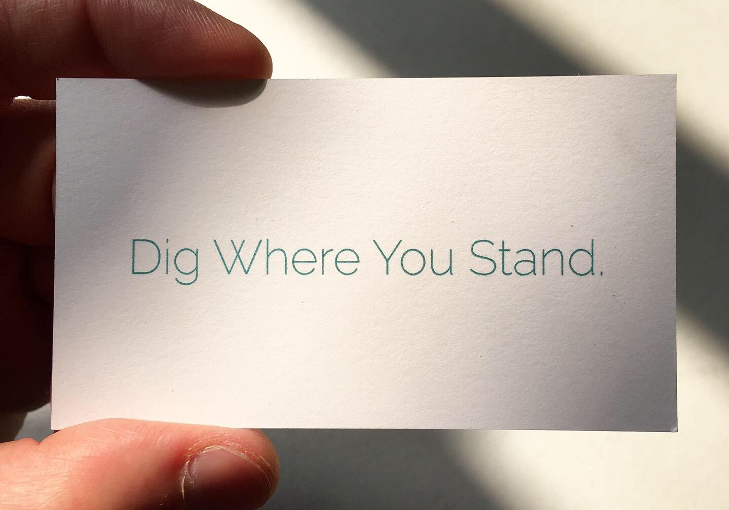 "A small card reads ""Dig Where You Stand"""